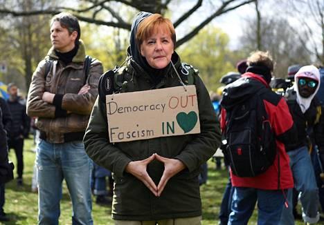 Merkelin kasvokuvasta tehdyllä naamarilla varustautunut mielenosoittaja Berliinissä tiistaina.