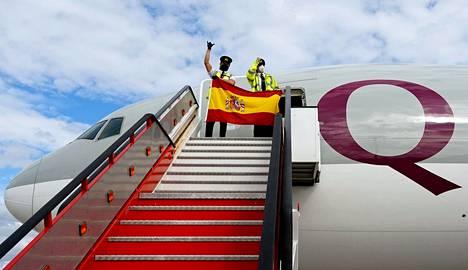 Shanghaista saapuneen, lääkintätarvikkeita kuljettaneen koneen pilotit heiluttivat Espanjan lippua koneen laskeuduttua Madridin Barajas Adolfo Suarez -lentokentälle sunnuntaina.