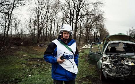 Etyjin tarkkailija tutki auton jäänteitä Mariupolin lähellä maanantaina.