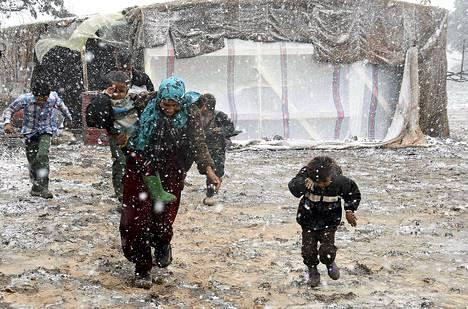 Syyrialaiset pakolaiset juoksivat suojaan lumelta pakolaisleirillä Itä-Libanonissa keskiviikkona.