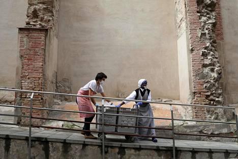 Nunna ja avustaja toimittavat ruokaa kodittomille ihmisille Ravalin alueella Barcelonassa.