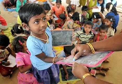 Intialaislapsi harjoitteli kirjoittamista liitutaululle Bangaloressa.