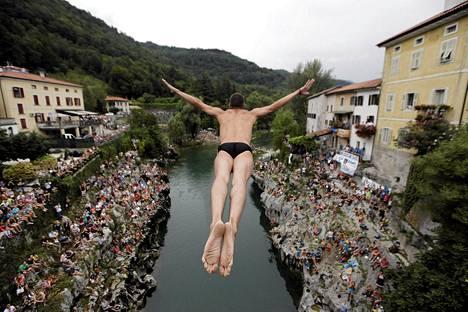 Uimahyppääjä hyppää vanhalta sillalta yleisön reunustamaan Soča-jokeen kilpailussa Kanal ob Socin kylässä Sloveniassa.