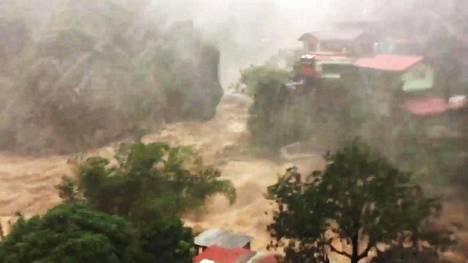 Filippiiniläisen Baguion kaupungin lähistöllä lauantaina otetussa kuvassa näkyy tulvaveden voima.