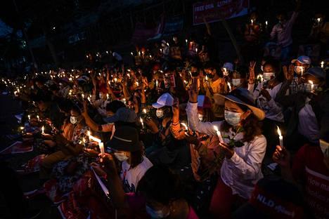 Mielenosoittajat pitelivät kynttilöitä lauantaina kuolleiden muistolle Yhdysvaltain suurlähetystön edessä Yangonin kaupungissa sunnuntaina.