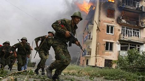 Georgialaisia sotilaita juoksi liekehtivän rakennuksen ohi Venäjän pommittamassa Gorin kaupungissa 9. elokuuta 2008. Venäläiskoneen asuinrakennukseen pudottaman pommin kerrottiin tappaneen ainakin viisi ihmistä. Gori sijaitsee Etelä-Ossetian ulkopuolella, eli tällöin taistelut olivat jo levinneet Georgian hallinnon alla olleille alueille.