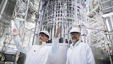 Projektinjohtajat Jean-Pierre Mouroux (vas.) Areva-Siemensistä ja Jouni Silvennoinen Teollisuuden Voimasta reaktorialtaassa. Heidän takanaan on reaktorin paineastian kansi, jossa näkyy myös säätösauvakoneisto.