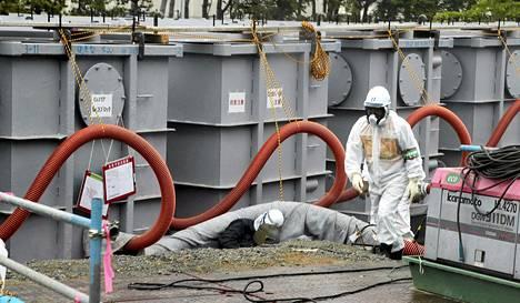 Säteilyturvapukuun pukeutunut työntekijä käveli Fukushima Daiichin ydinvoimala-alueella kesäkuussa.