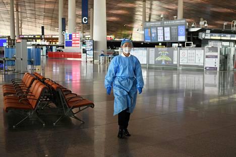 Pekingin lentokentällä on ollut hiljaista sen jälkeen, kun maa asetti uusia matkustusrajoituksia 18. kesäkuuta lähes puolelle miljoonalle Pekingin alueen asukkaalle. Suojavarusteisiin pukeutunut työntekijä kuvattiin kävelemässä lentokentällä.