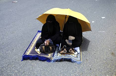Naiset istuivat kadulle rukoilemaan Sanaassa perjantaina.