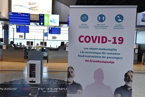 Käsidesi ja THL:n kehoitus lukea matkustajille tarkoitetut koronavirusohjeet Turun lentoasemalla tiistiana.