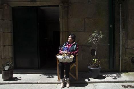 """Eläköityneen ompelijan Augusta Santanan huvi on katsella kotikadulla tungeksivia espanjalaisia turisteja sekä pyhiinvaeltajien virtaa. """"Korona hiljensi kadut aavemaisiksi, ja elämä tuntuu surulliselta"""", hän sanoo Valençan rajakaupungissa."""