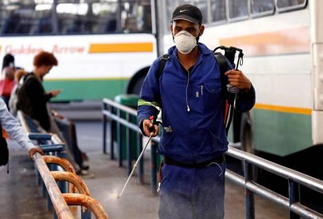 Työntekijä suihkuttaa desinfiointiainetta kaiteisiin bussivarikolla Kapkaupungissa.