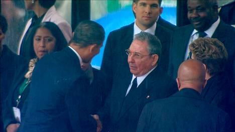 Yhdysvaltain presidentti Barack Obama kätteli Kuuban presidenttiä Raúl Castroa Mandelan muistotilaisuudessa. Kuvakaappaus Etelä-Afrikan televisioyhtiön lähetyksestä.