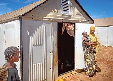 Nuori somalinainen perheineen uudenlaisen moduulimökin ovella Koben pakolaisleirillä Dollo Adossa Etiopiassa. Ensimmäiset mökit ovat olleet testikäytössä heinäkuusta asti.
