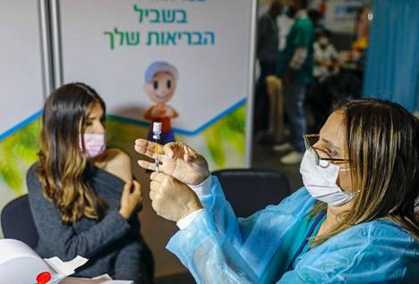 Terveydenhoitaja valmistautui rokottamaan nuorta israelilaisnaista Jerusalemissa 14. tammikuuta.