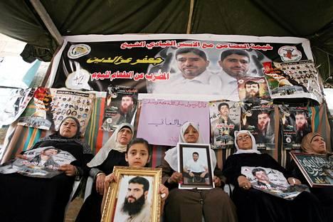 Palestiinalaiset näyttävät Israelin vankiloissa olevien sukulaistensa kuvia syömälakkolaisia tukevassa mielenosoituksessa.