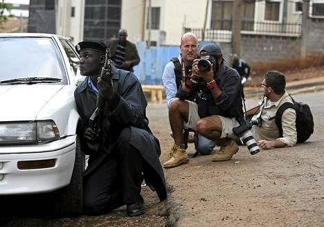 Poliisi ja valokuvaajat suojautuivat kuultuaan laukauksia lähellä Westgaten ostoskeskusta Nairobissa maanantaina.