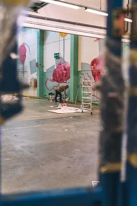 """""""Nykyaikaiseksi maagisen realismin"""" tekijäksi kuvailtu Taneli Stenberg maalaamassa Concreate-teostaan huhtikuun alussa."""