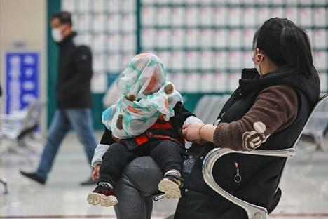 Nainen vieraili lapsensa kanssa wuhanilaisessa sairaalassa maaliskuun puolivälissä.