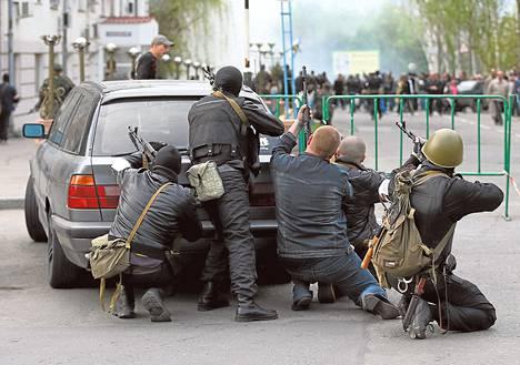 Venäjän-mielisten asemiesten joukko suojautui auton taakse Luhanskissa Itä-Ukrainassa tiistaina.