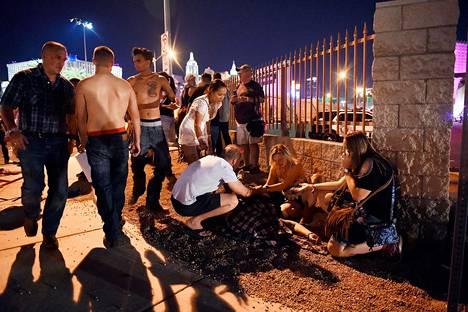 Ihmiset auttoivat loukkaantunutta festivaalialueen ulkopuolella.