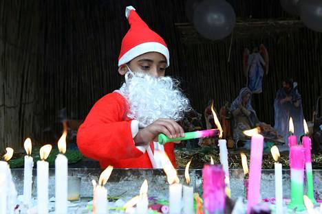 Tonttuasuinen poika sytytti kynttilöitä Luoteis-Intian Amritsarissa joulupäivänä keskiviikkona.