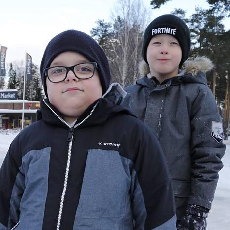 Yhdeksänvuotiaat Valtteri Tervo (vas.) ja Lenni Nevasmaa kantoivat ämpärillä hiekkaa heidän takanaan olevaan risteykseen jumiin jääneelle bussille, jolla auttamassa oli jo aikuisia. Bussi pääsi sitten jatkamaan matkaansa.