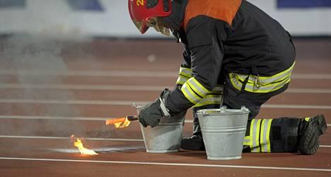 Palomies sammutti katsomosta heitetyn soihdun Suomen ja Espanjan välisessä MM-karsinnassa syyskuussa 2013.