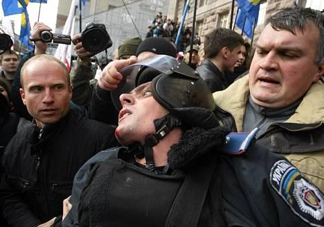 Mielenosoittajat pyrkivät mellakkapoliisien ohi kaupungintalolle Kiovassa keskiviikkona.