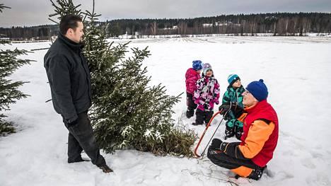 Kuusitilan isäntä Pekka Anttonen auttoi Mea Pylväläistä sekä Saana ja Teemu Tiirikaista kuusen sahaamisessa. Timo Tiirikainen (vas.) kantaa kuusen traktorin lavalle.