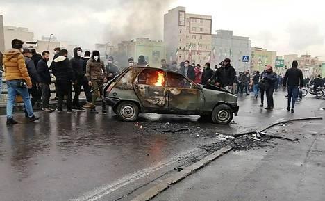 Mielenosoittajat kerääntyivät palavan auton ympärille Iranin pääkaupungissa Teheranissa viikonloppuna.