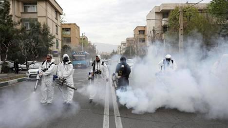 Suoja-asuihin pukeutuneet palomiehet puhdistivat katuja Iranin pääkaupungissa Teheranissa 18. maaliskuuta.