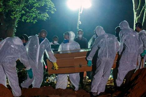 Hautaustyöntekijät kantoivat arkkua Vila Formosan hautausmaalla São Paulossa Brasiliassa torstaina.