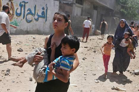 Asukkaat juoksivat turvaan Israelin ilmaiskulta keskiviikkona Gazan kaupungissa.