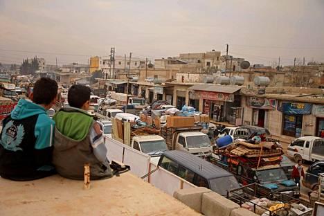 Pojat seurasivat ihmisten pakenemista taistelujen tieltä Hazanon kaupungissa Idlibissä maanantaina.