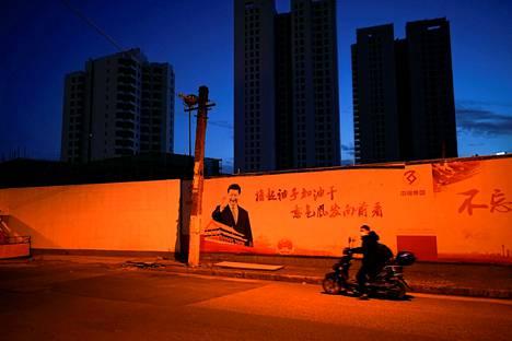 Kasvosuojainta käyttänyt mies ohitti presidentti Xi Jinpingiä esittäneen julisteen Kiinan Shanghaissa maaliskuun 16. päivänä.
