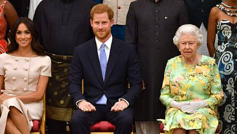 LKS 20210308 (FILES) In this file photo taken on June 26, 2018 (L-R) Meghan, Duchess of Sussex, Britains Prince Harry, Duke of Sussex and Britains Queen Elizabeth II pose for a picture during the Queens Young Leaders Awards Ceremony at Buckingham Palace in London. - Britains royal family on Sunday braced for further revelations from Prince Harry and his American wife, Meghan, as a week of transatlantic claim and counter-claim reaches a climax with the broadcast of their interview with Oprah Winfrey. LEHTIKUVA / AFP / JOHN STILLWELL FILES - US - BRITAIN - ROYALS - MEGHAN - HARRY