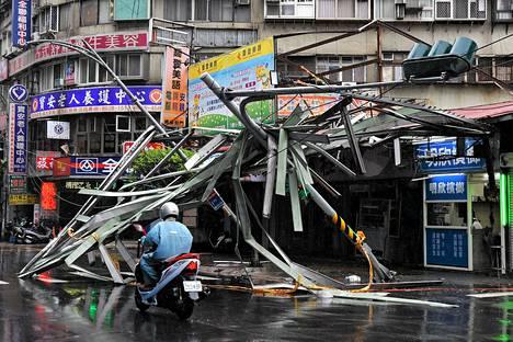 Mies ajoi taifuuni Soulikin aiheuttamien tuhojen ohi lauantaina Taipeissa. Tuuli on puhaltanut kovimmillaan jopa 220 kilometrin tuntivauhtia ja vettä tullut enimmillään melkein metri kahdessa päivässä.