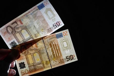 Väärennetty ja aito (alhaalla) 50 euron seteli vuonna 2011.