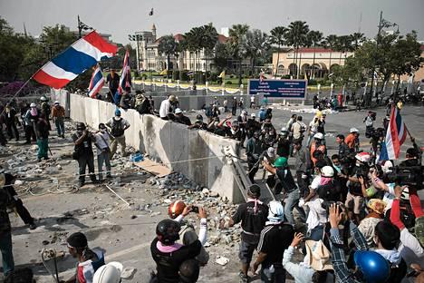 Hallituksenvastaiset mielenosoittajat mursivat aidan hallituksen päämajan ympäriltä tiistaina Bangkokissa.