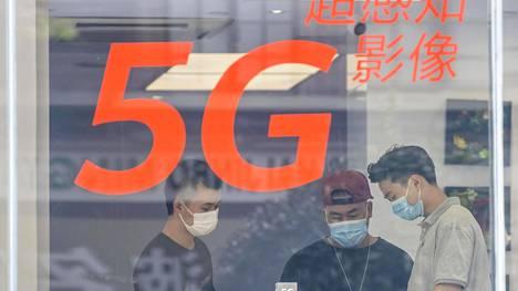 Asiakkaita Huawein myymälässä Shanghaissa kesällä 2020. Ikkunassa mainostetaan 5g-puhelimia.
