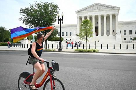 Aktivisti heilutti sateenkaarilippua Yhdysvaltain korkeimman oikeuden edessä maanantaina sen jälkeen, kun oikeus päätti vuonna 1964 laaditun kansalaisoikeuslain suojelevan sukupuoli- ja seksuaalivähemmistöjä syrjinnältä työelämässä.