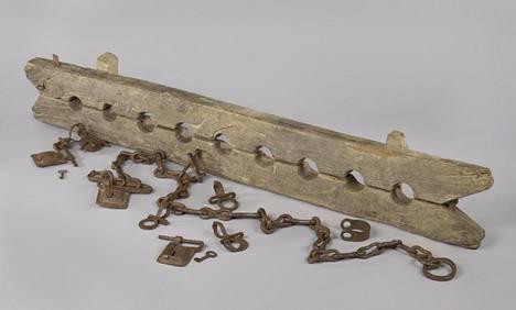 """Jalkapuu ja kuudet eri kahleet usean orjuutetun kiinnipitämistä varten. Osa Rijksmuseumin """"Orjuus""""-näyttelyä."""