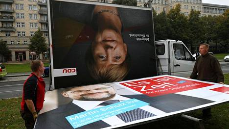 Työmiehet poistivat kristillisdemokraattien johtajan, liittokansleri Angela Merkelin vaalimainoksen Berliinissä.