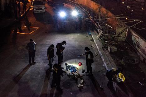 JULMA HUUMESOTA. Vuonna 2016 Filippiinien presidentiksi valittu Rodrigo Duterte on jatkanut jo Davaon miljoonakaupungin pormestarina aloittamaansa huumeiden vastaista sotaa, jossa huumekauppiaiksi epäiltyjä on surmattu armotta. Kuvassa poliisi tutkii kadulle surmattua miestä Manilassa kesällä 2017.