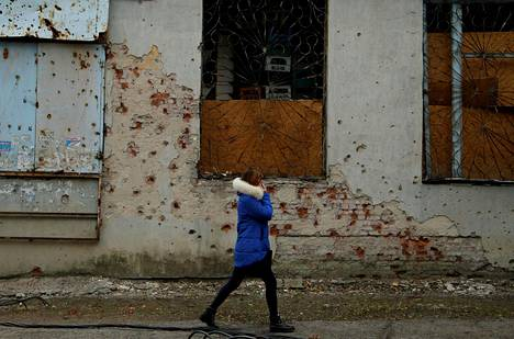 Nainen käveli tulituksessa kärsineen liiketilan ohi Donetskissa maanantaina.