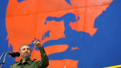 """Fidel Castro otti sormi pystyssä vastaan yleisön suosionosoitukset vuoden 2005 kesäkuussa Havannassa pidetyssä urheilukilpailussa, jossa taustaseinässä oli kuva vallankumousjohtaja Ernesto """"Che"""" Guevarasta."""