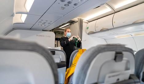 Matkustamohenkilökunta käyttää Finnairin lentokoneissa kasvomaskeja. Anna Törrönen näyttää turvavöiden käyttöä.