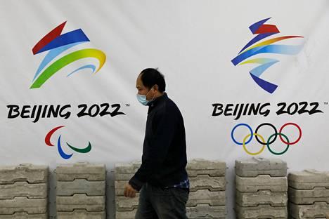 Mies käveli Pekingin talviolympialaisia mainostavan lakanan edessä Pekingissä tammikuussa.